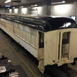 Car 1194's restoration progresses with body work, primer, and roof coating.
